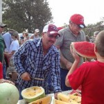 Chad Wooldridge cuts up watermelon for the Watermelon Feed