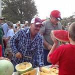 Chad Wooldridge cuts up watermelon for the Watermelon Feed