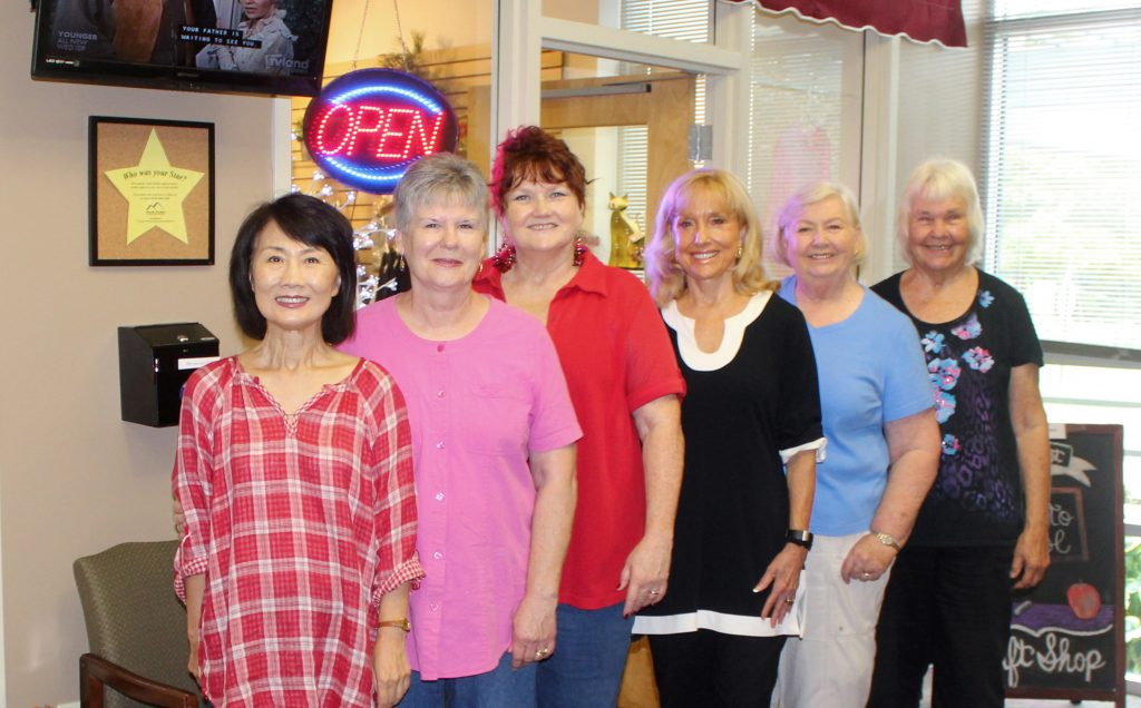 """The Artist League hung a new exhibit with the theme of """"Orange"""" at Ozark Health Medical Center. Standing in front of the Hospital Auxiliary Gift Shop are Yun Kim, Joyce Hubbard, Mt. View; Sue Pico, Clinton; Charlotte Rierson, Fairfield Bay; Jan Cobb, Greers Ferry; and Exhibit Coordinator Joyce Hartmann, Choctaw."""